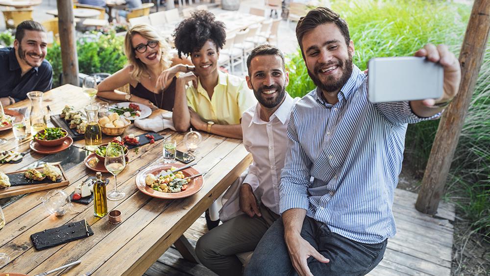 gli ospiti del ristorante all'aperto si fanno un selfie insieme