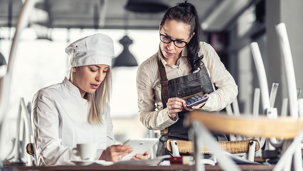 chef e cameriere del ristorante millenario che parlano a un tavolo